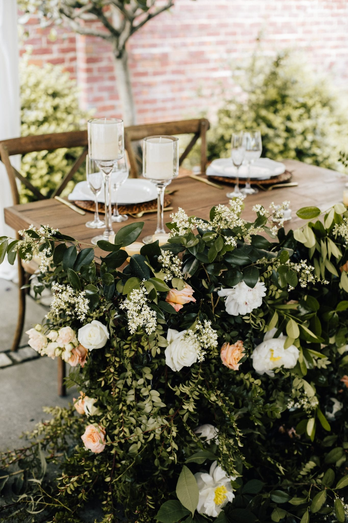 Garden wedding sweetheart table with rattan chargers and crystal candlesticks and overflowing floral arrangement
