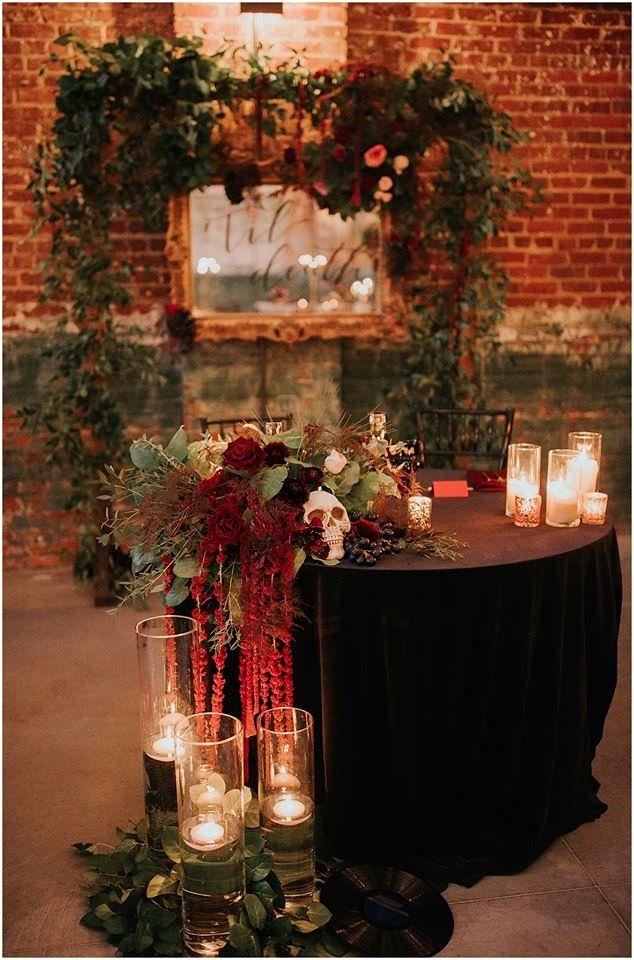 Sweetheart wedding table with marsala candles, floral arrangement, and blush velvet chairs
