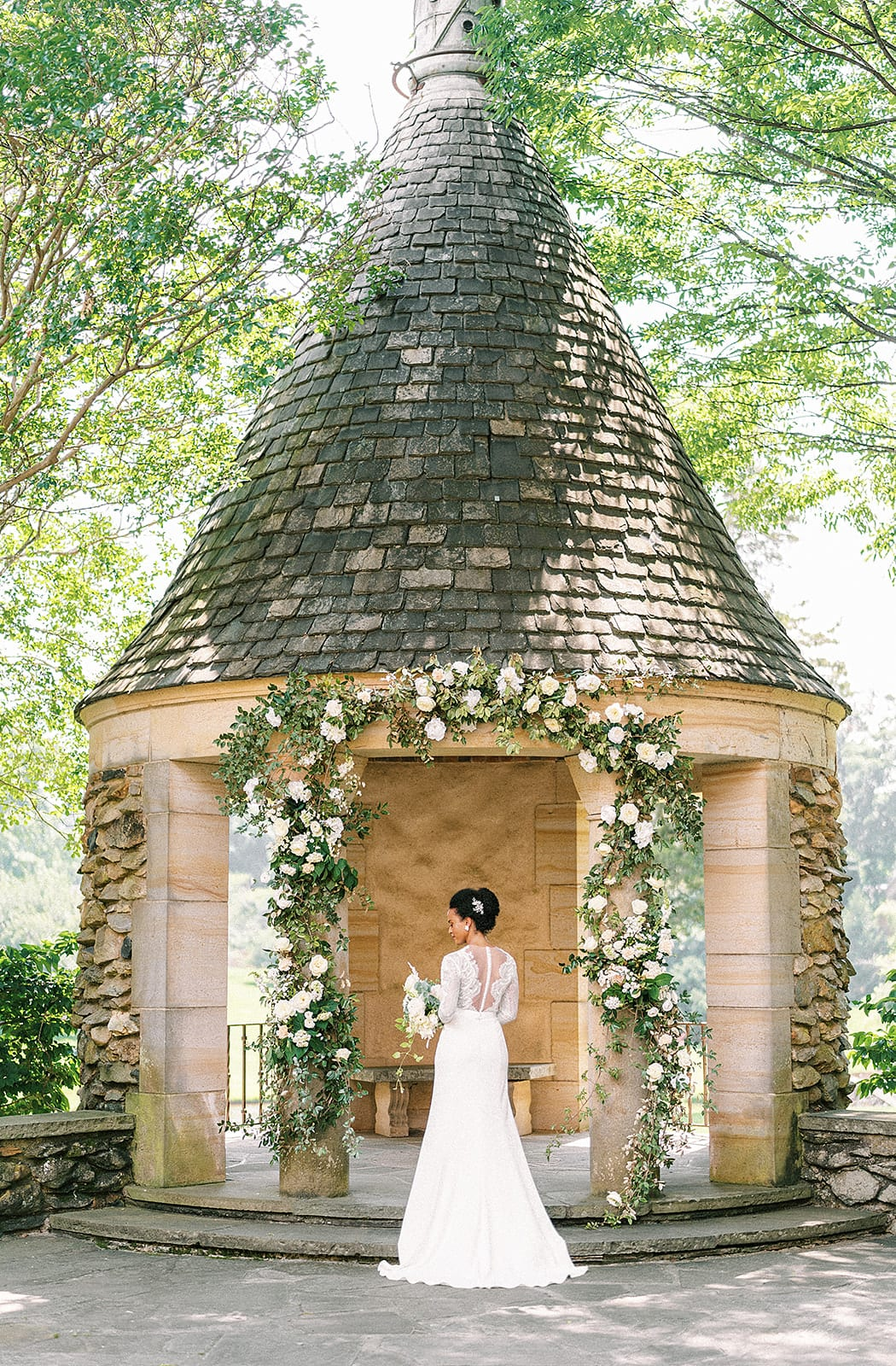 Bride in a wedding gown under the stone gazebo and floral arch at Graylyn Estate
