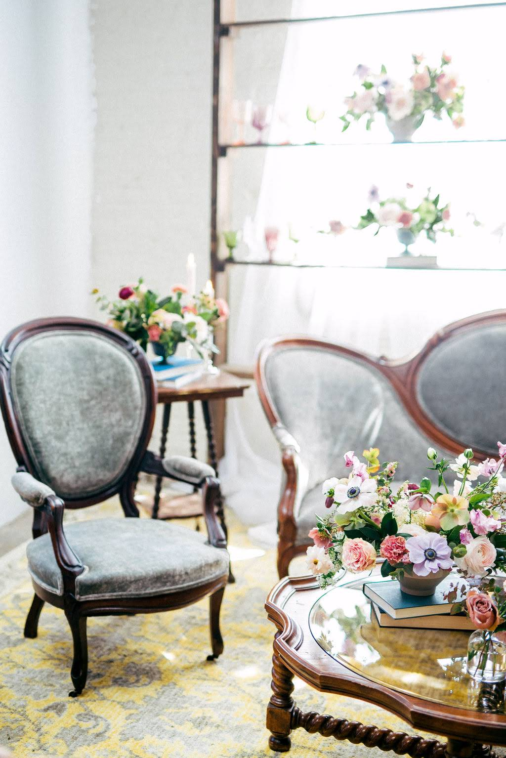 Grey velvet vintage chairs with antique books and spring wedding florals and yellow rug