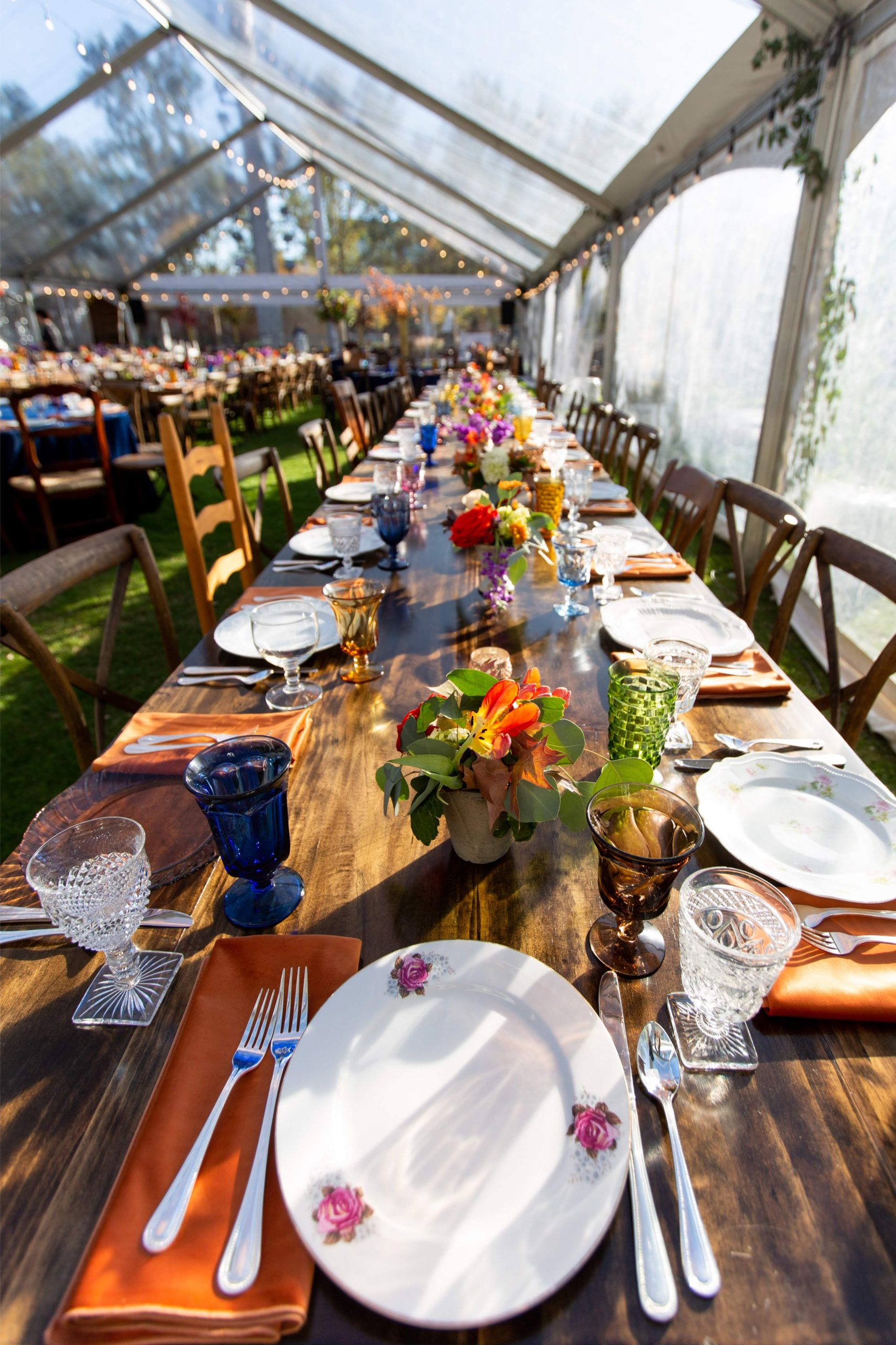 Large Friendsgiving table setting with antique china, colorful vintage goblets, and small floral arrangements inside a clear tend with string lights and greenery